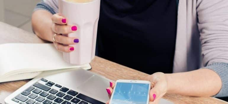 A woman holding a phone and a cup of coffee.