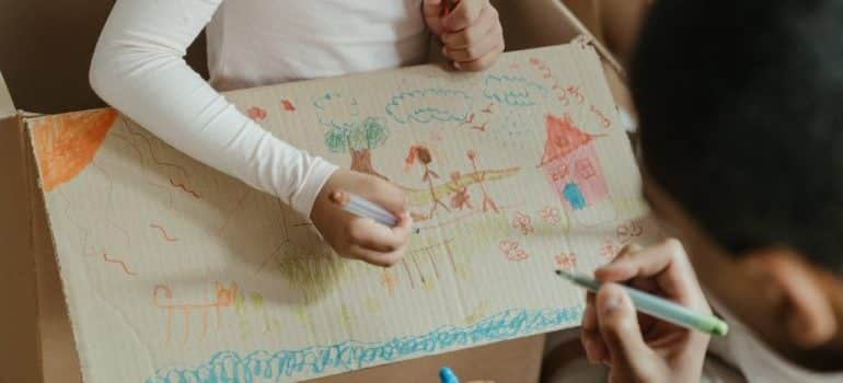 kids drawing on a cardboard box