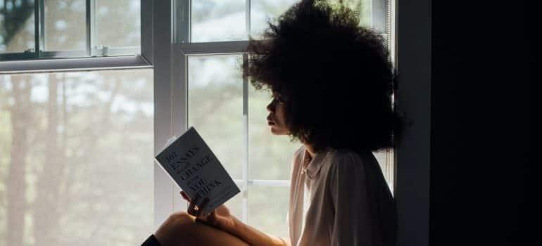 woman-sitting-on-window-reading-book