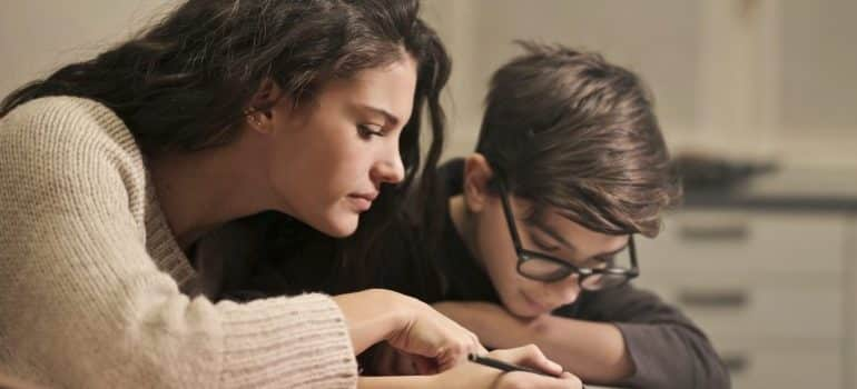 woman helping kid with the homework